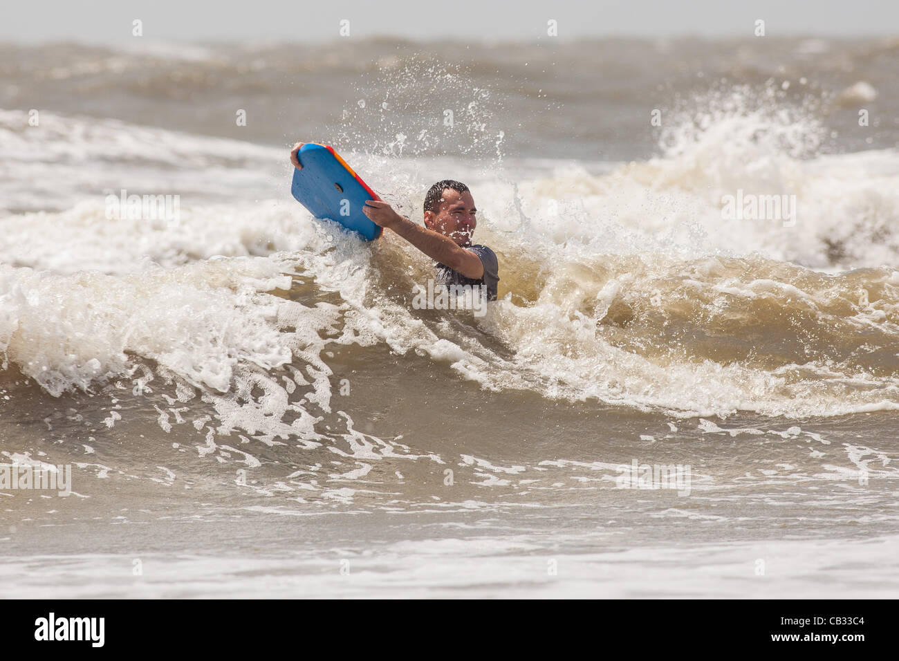 USA. A beach goer tries to stay above strong waves as Tropical Storm Beryl brushes past the South Carolina coast - Stock Image