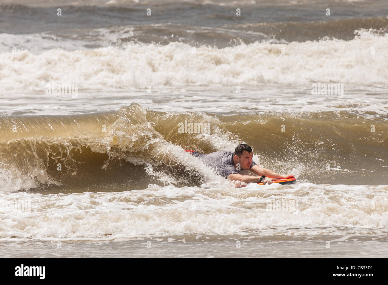 USA. A beach goer body surfs strong waves as Tropical Storm Beryl brushes past the South Carolina coast on May 27, - Stock Image