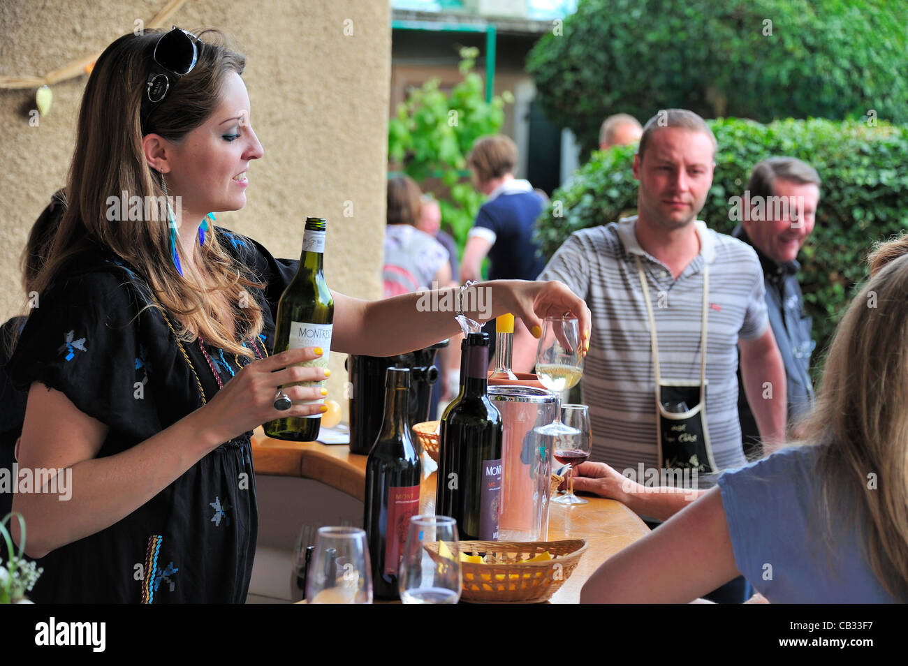 A Swiss wine producer pours a sample of her wine for a visitor during a 'caves ouvertes' (open cellars) event. It Stock Photo