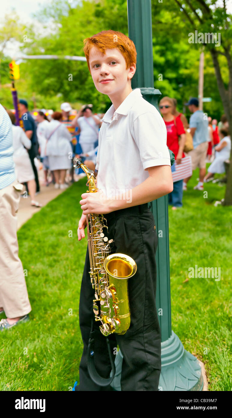 Red-haired boy with alto saxophone, after marching with his school band  the Merrick Memorial Day Parade on Monday, - Stock Image