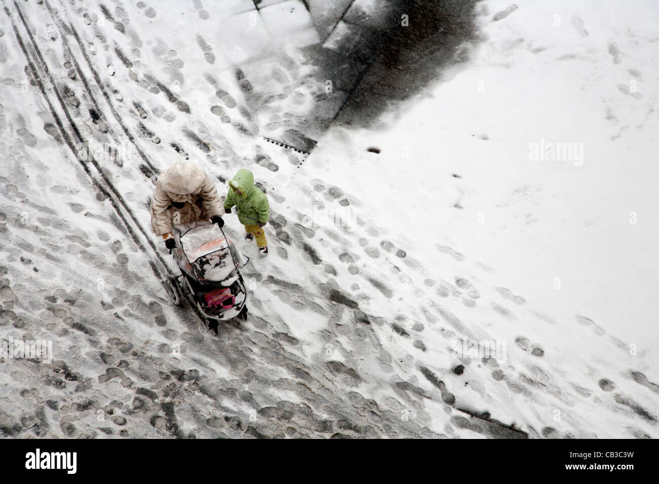 woman and children in snowfall - Stock Image