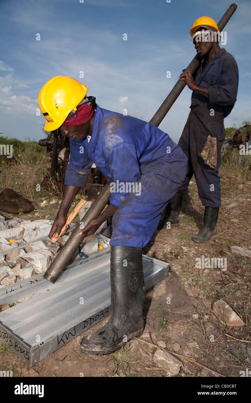 Local Kenyan field assistants retrieving HQ core from core barrel on gold exploration project, Western Kenya, Africa - Stock Image