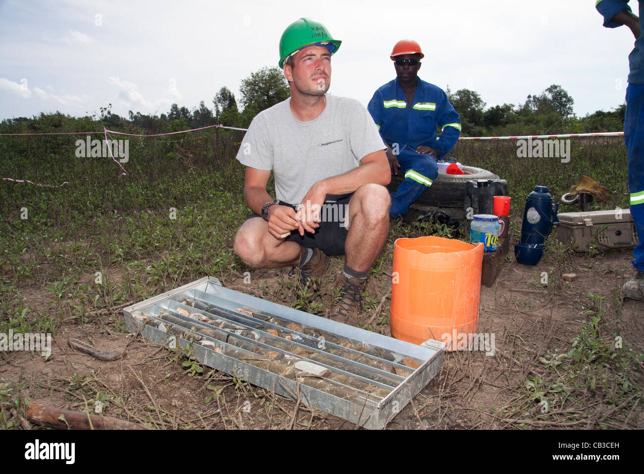 Male geologist inspecting diamond drill core for gold at the drill rig site, Kenya - Stock Image