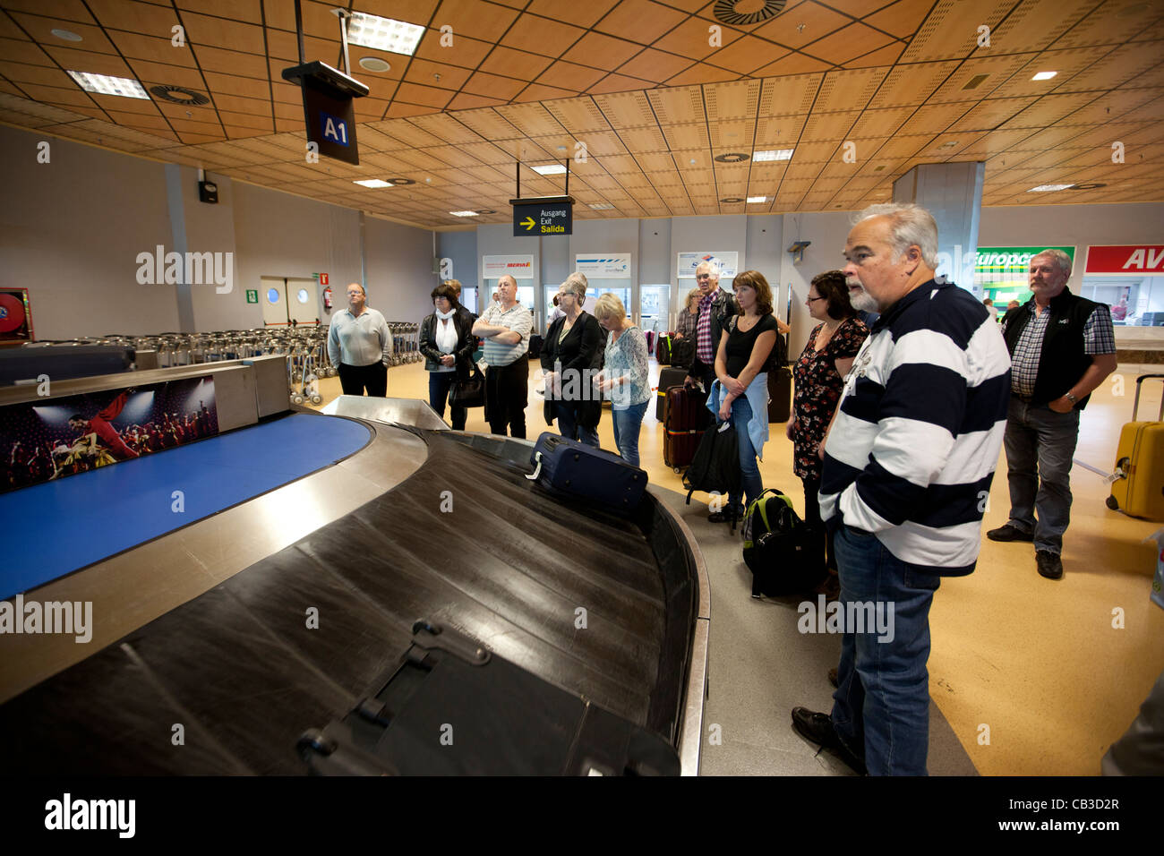 Tourists waiting for their luggage, Tenerife, Canary Islands, Spain. - Stock Image
