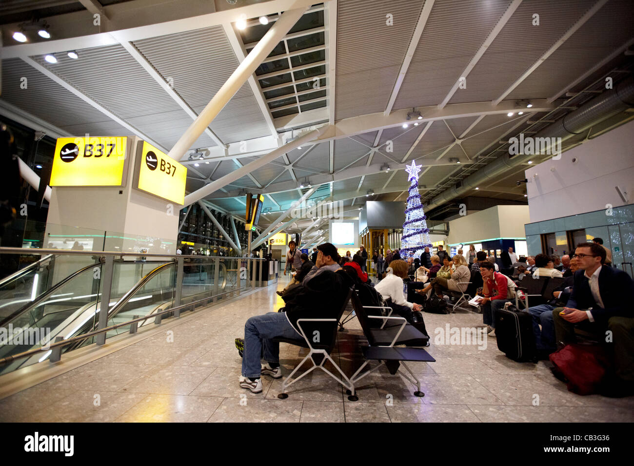 passengers waiting at gate in terminal 5 heathrow - Stock Image