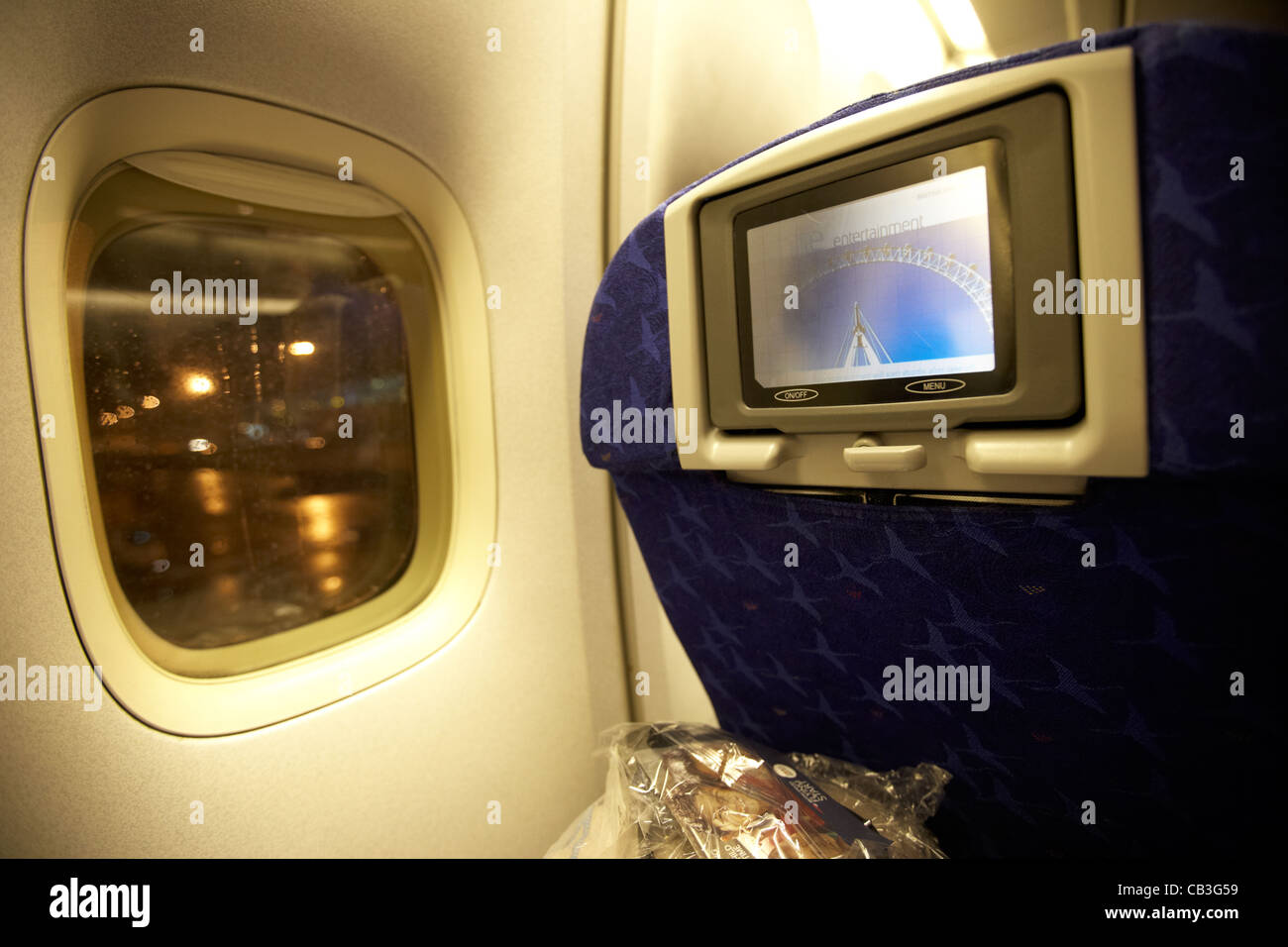 passengers individual entertainment screen on board a 747 passenger aircraft night flight - Stock Image