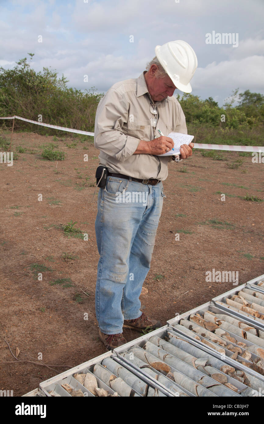 Senior geologist inspects diamond drill core on a daily trip to the drill rig in Kenya, Africa - Stock Image
