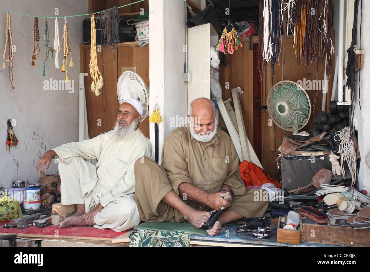 Two shoe repair men at work in their