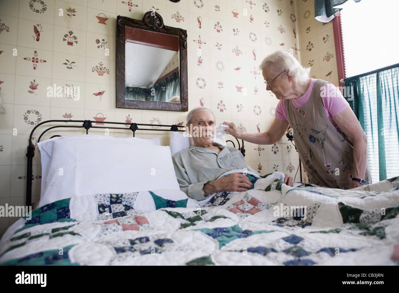 Senior woman affectionately tending to bedridden senior man - Stock Image