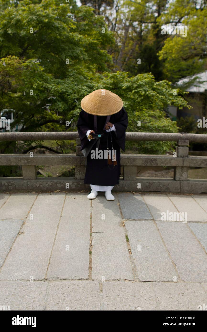 A shinto monk collection money outside Ise grand shrine, Ise, Honshu, Japan, Asia. - Stock Image