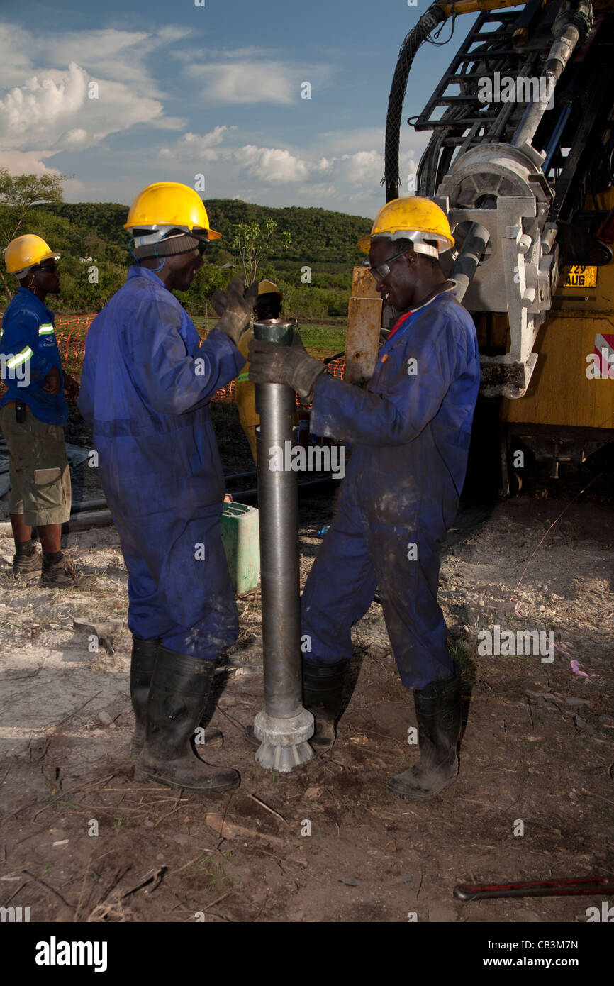 Kenyan drillers offside assistants changing reverse circulation drill bit. - Stock Image