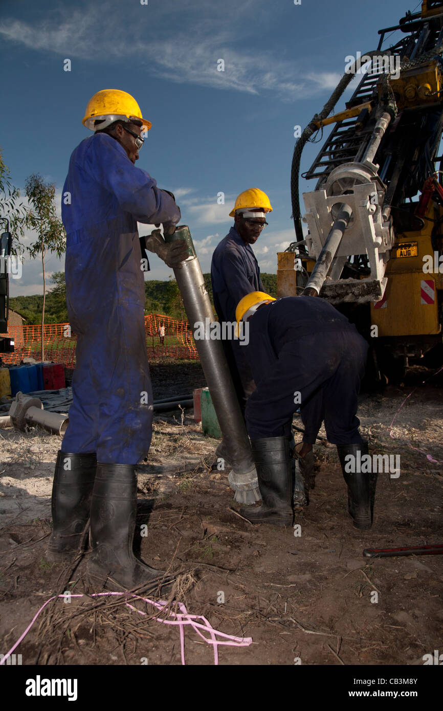 Kenyan drillers offside assistants changing reverse circulation drill bit - Stock Image