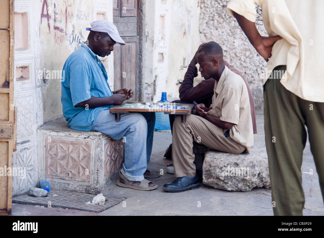 Men playing draughts board game in the back streets of Mombasa, Kenya - Stock Image