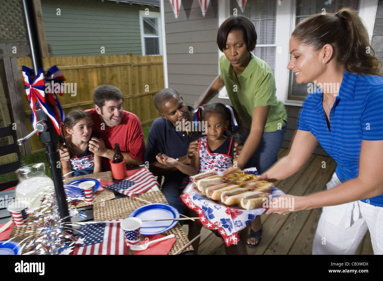 Two Families On Backyard Patio Enjoying A Cookout On The