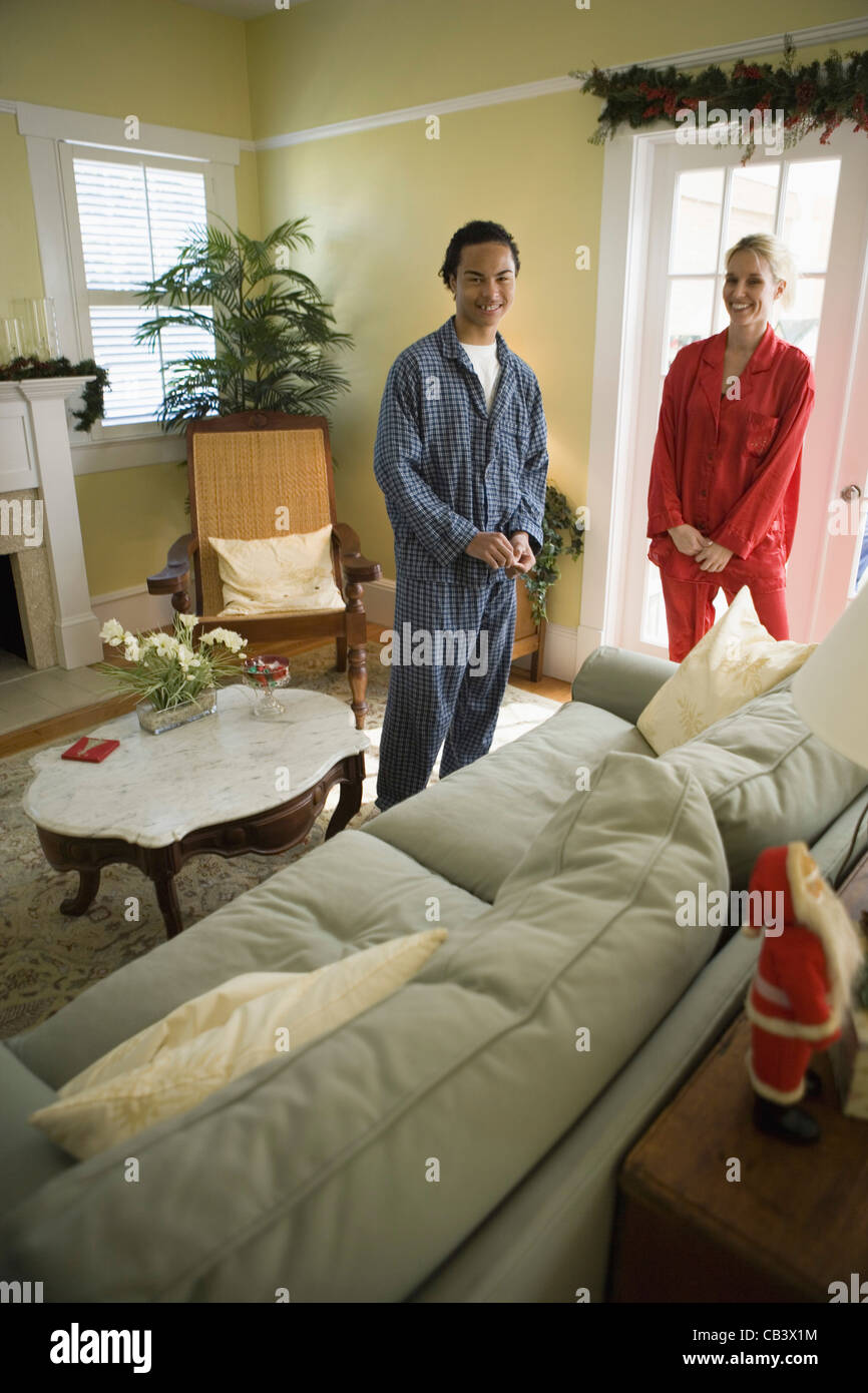 Teenage Boy With His Mother In Pajamas Standing In Living Room