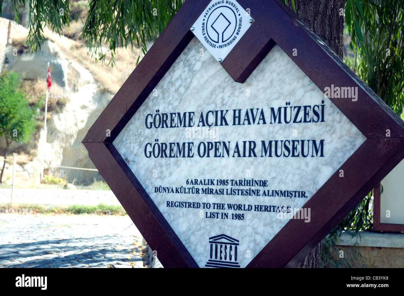The sign for the Goreme Open Air museum of tufa rock formations in Cappadocia records its World Heritage Site listing - Stock Image