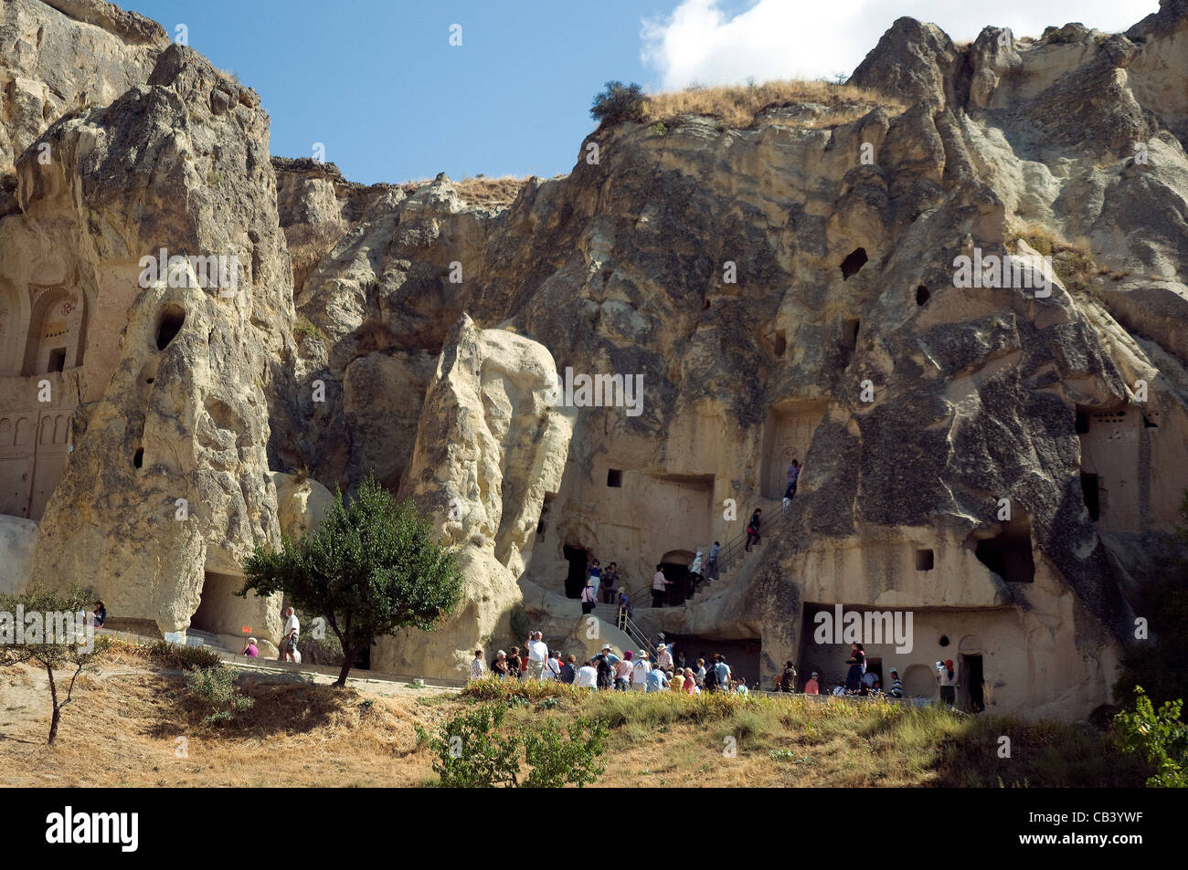 Tourists explore the Goreme Open Air museum's volcanically formed rock formations, caves and churches in Cappadocia - Stock Image