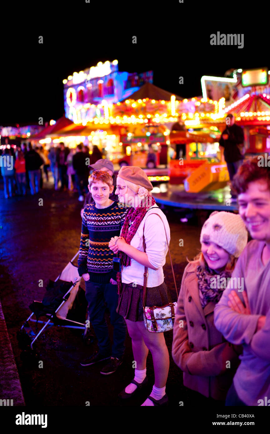 Young People looking entranced at the lights and sounds of the Aberystwyth annual November funfair fairground fair, - Stock Image