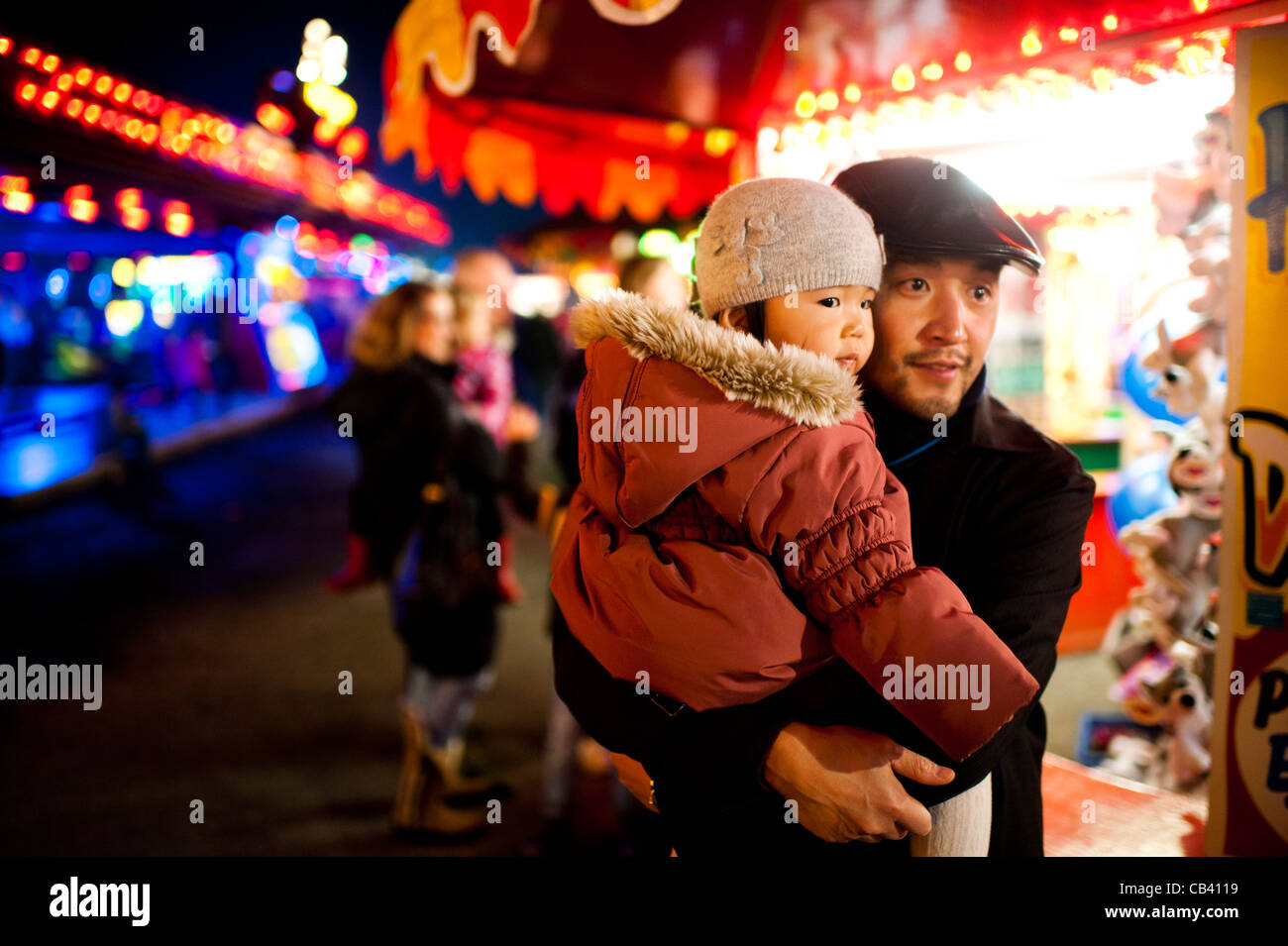 father daughter looking entranced at the lights and sounds of the Aberystwyth annual November funfair fairground - Stock Image
