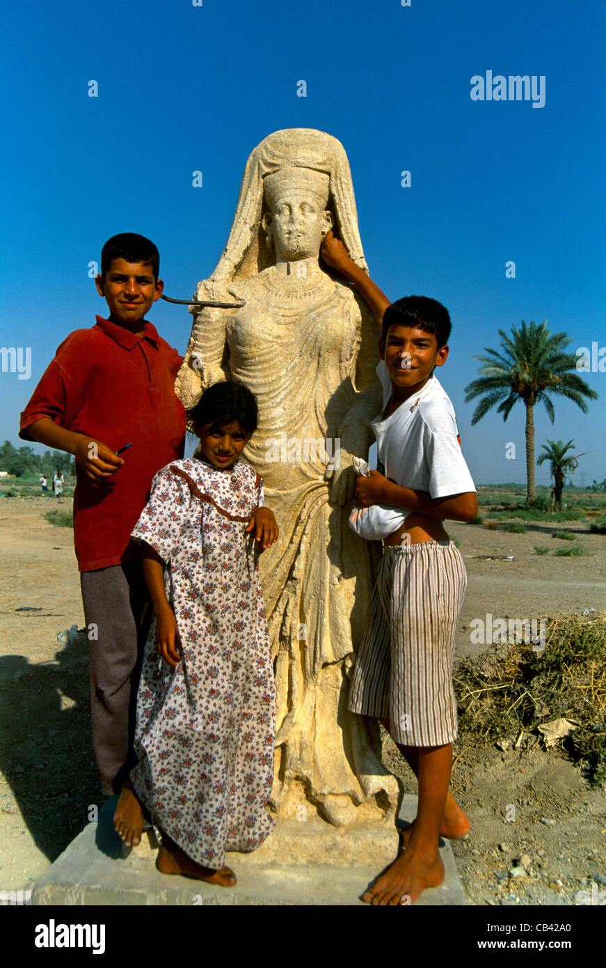 Iraq Ctesphone Children With Statue Of Queen From Hatra Al Mada'in - Stock Image