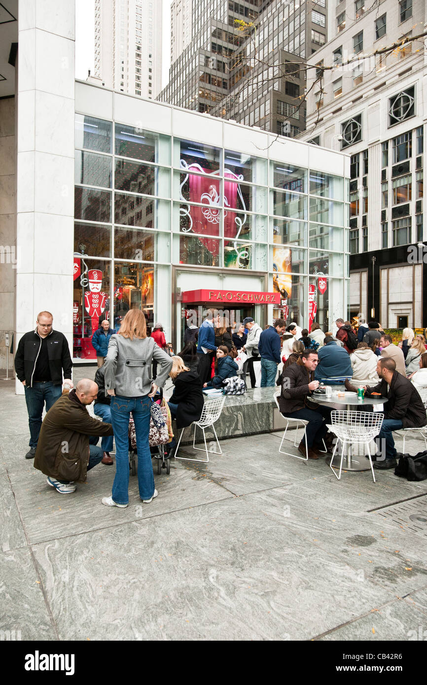 Christmas shoppers & passers by crowd the plaza in front of legendary FAO Schwartz toy store Fifth Avenue New - Stock Image