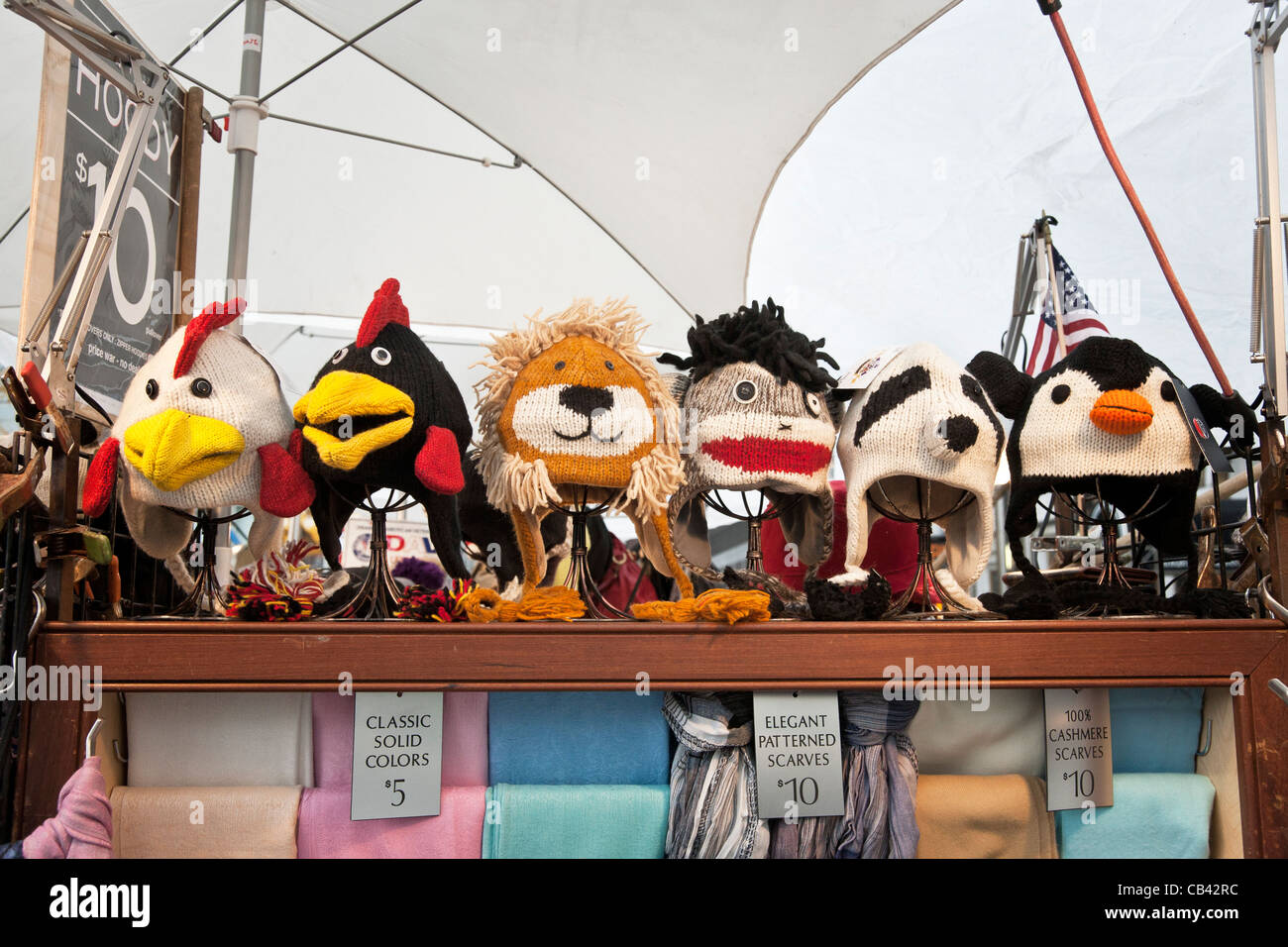 colorful anthropomorphic novelty winter cap caps displayed for sale on street vendors cart Fifth Avenue New York - Stock Image