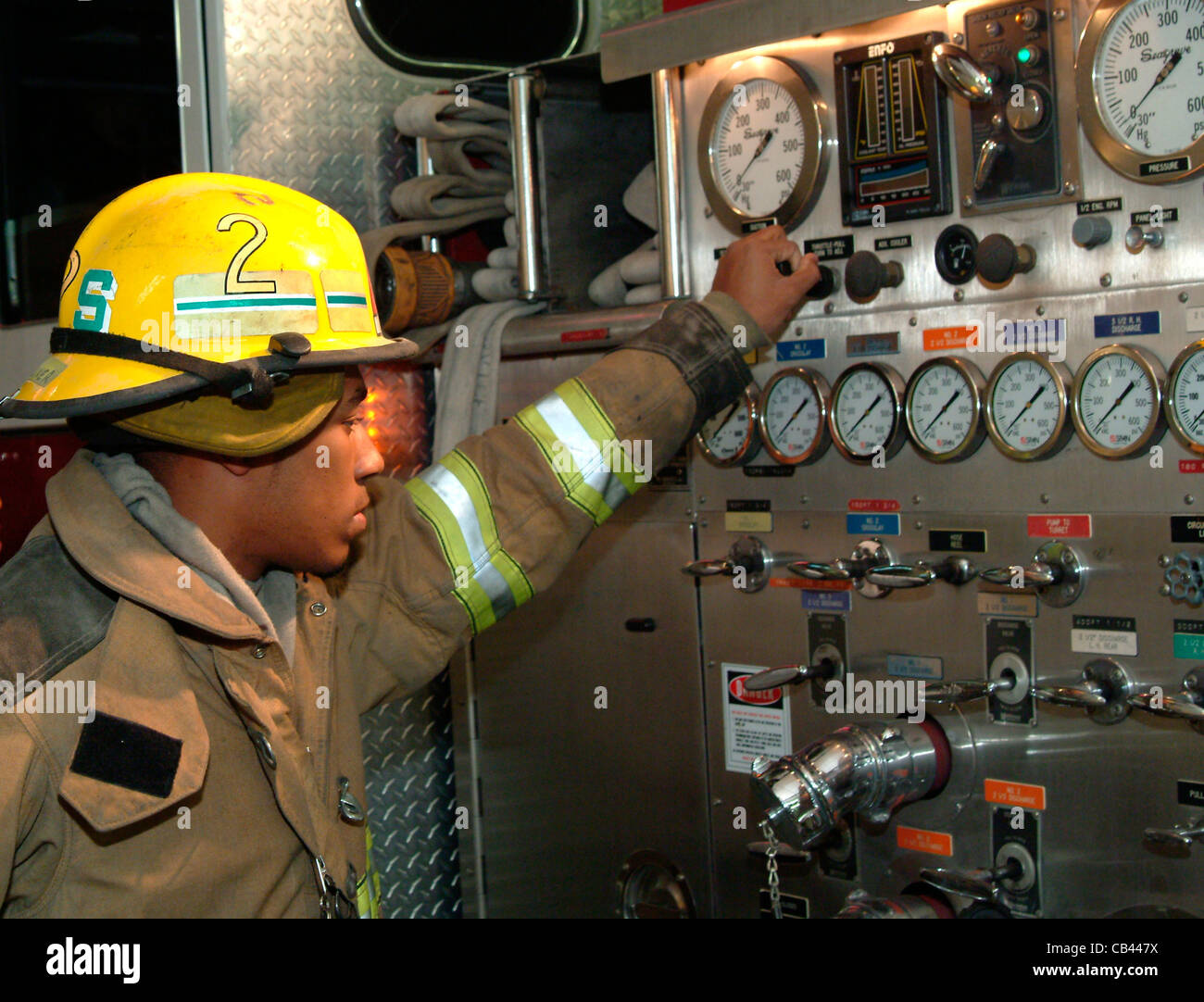 Black Fireman Stock Photos Images Alamy Fire Engine Pump Panel Diagram Firefighter Studies The Gages On Of A Truck During