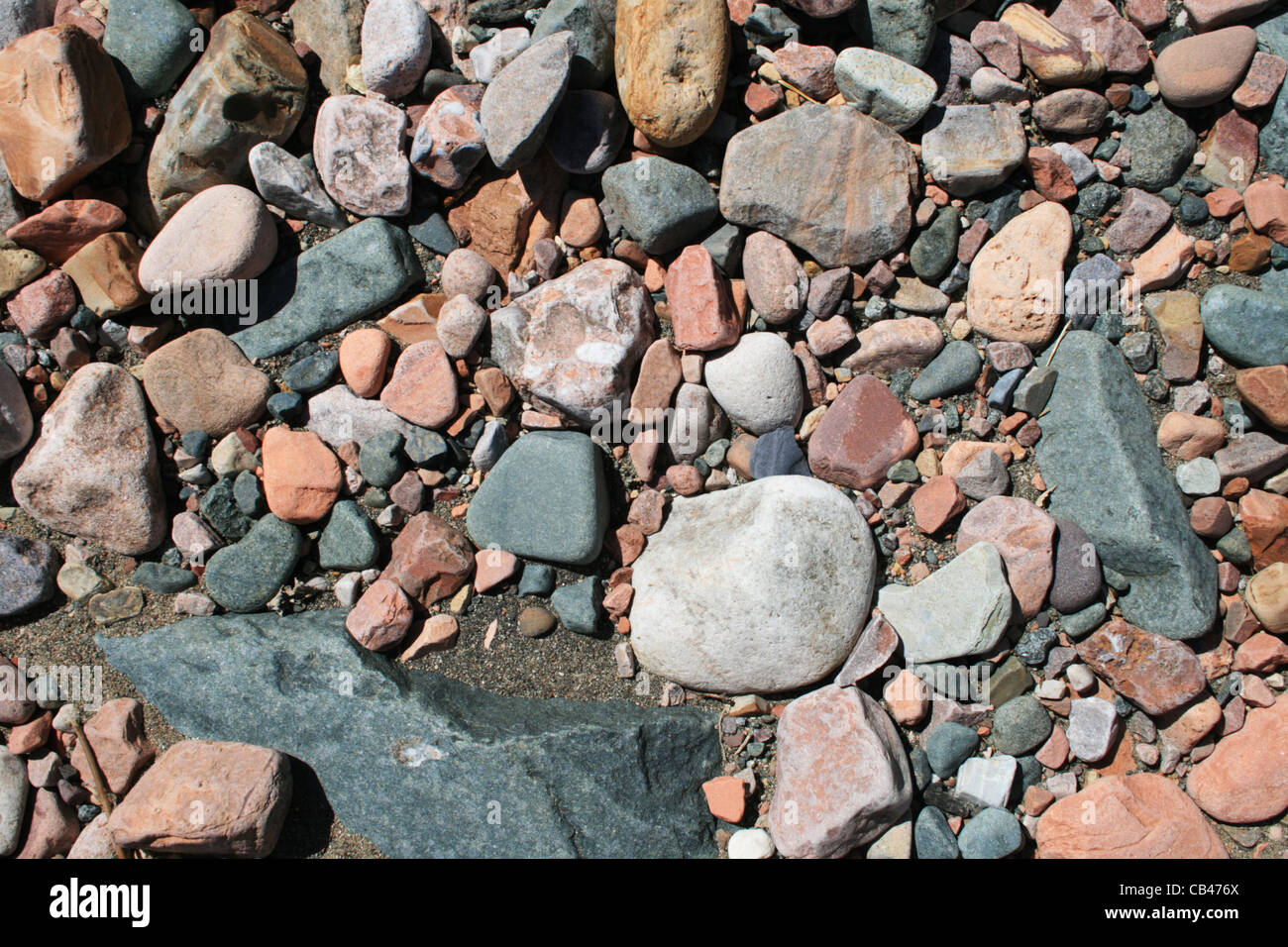 rounded smooth gray, white, and red rock and sand background - Stock Image