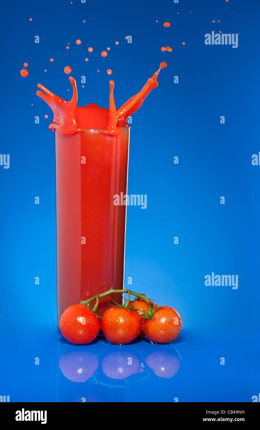 Splash of tomato juice in glass on blue background with cherry tomatoes laying nearby Stock Photo
