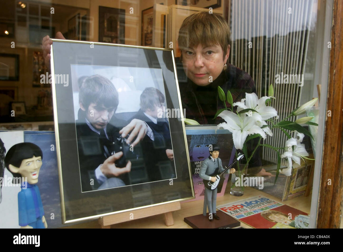 Meg Maloney creates a tribute to George Harrison in the window of the Penny Lane Gallery in Kemptown after his death Stock Photo