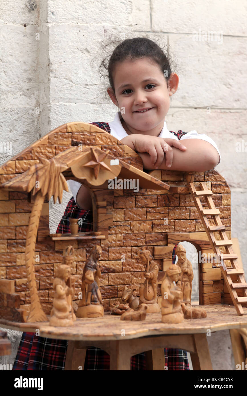 Girl with nativity crib at a souvenir shop close to the the Church of the Nativity, Bethlehem, Palestine - Stock Image