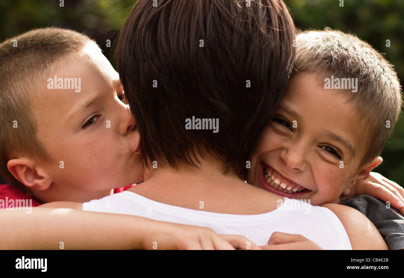 Two Brothers showing Love to there Mum with a cuddle and a kiss - Stock Image