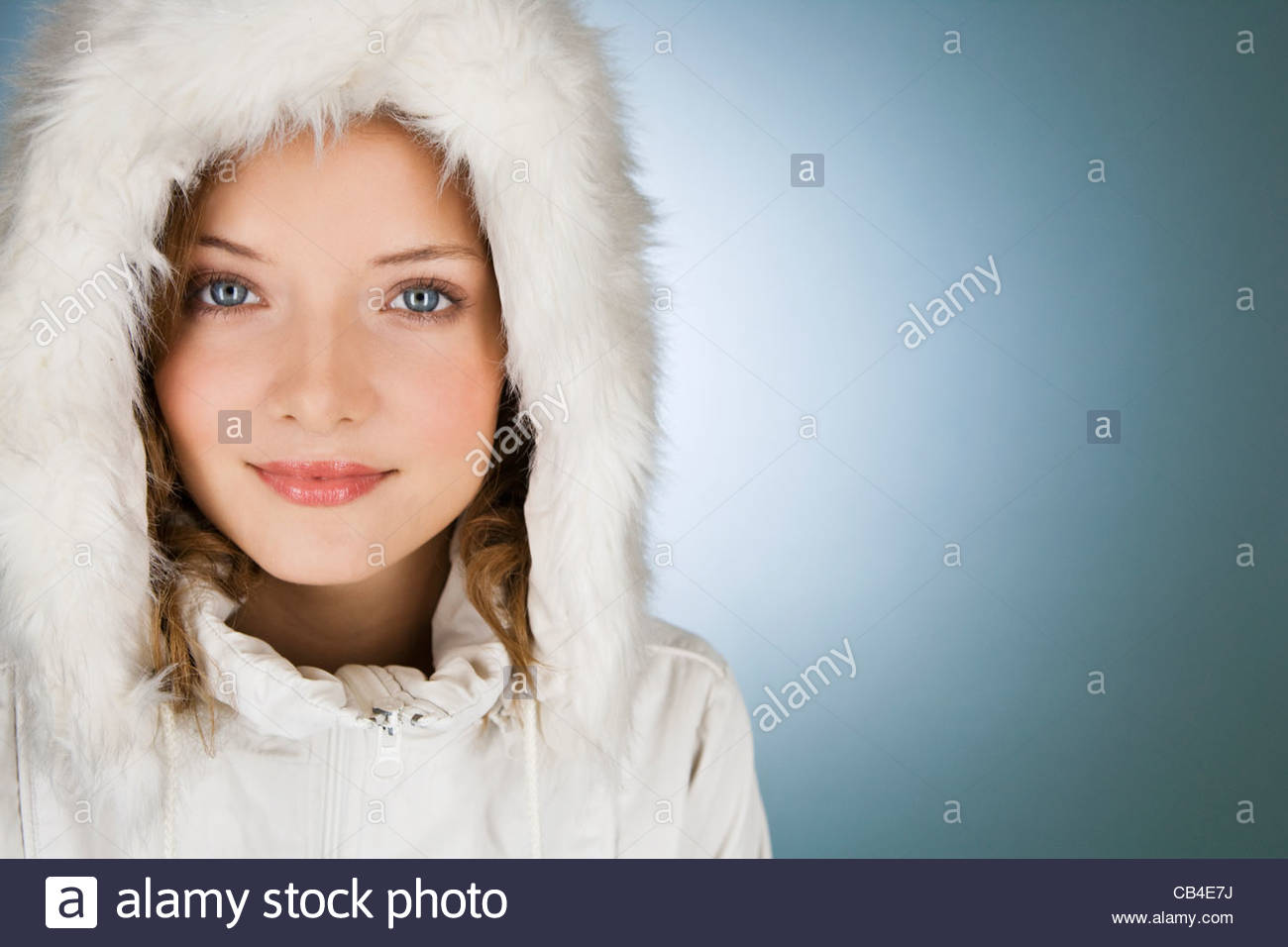 A young woman wearing a winter coat with a fur hood - Stock Image