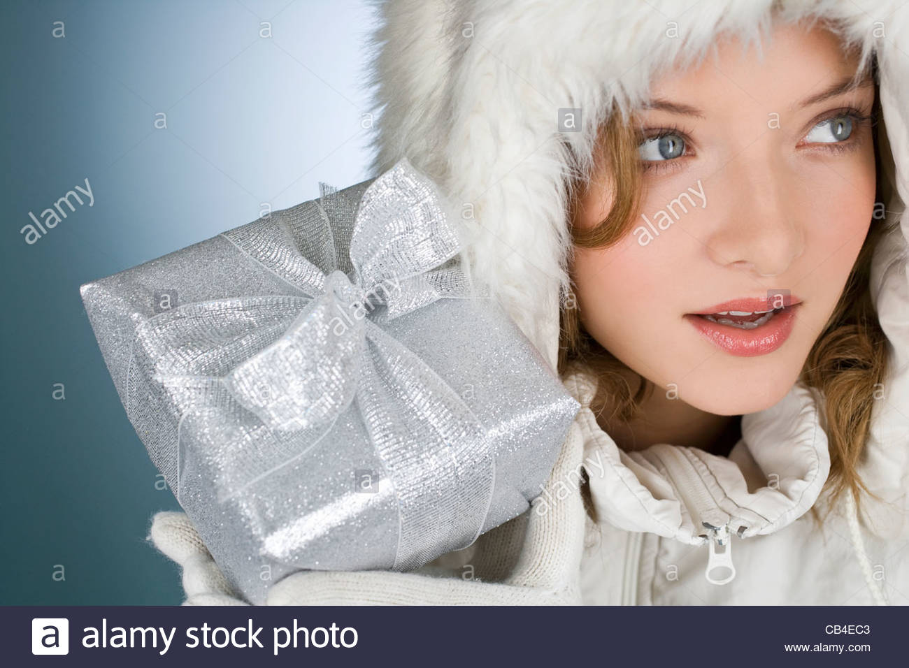 A young woman wearing a winter coat, holding a Christmas present - Stock Image