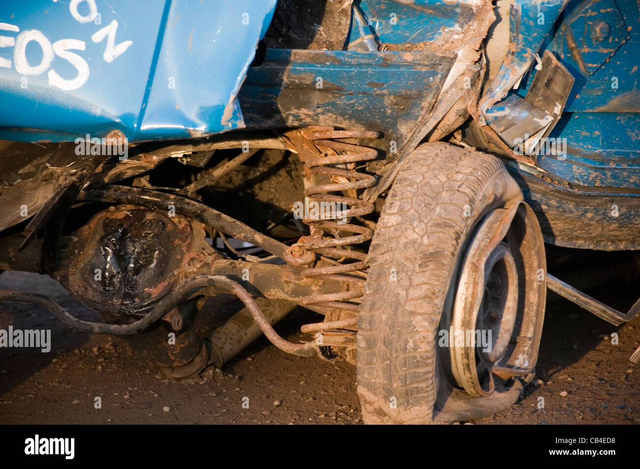 coil spring sprung axle suspension car cars wheel flat tire tyre rear crash crashed bent twisted steel stock banger - Stock Image