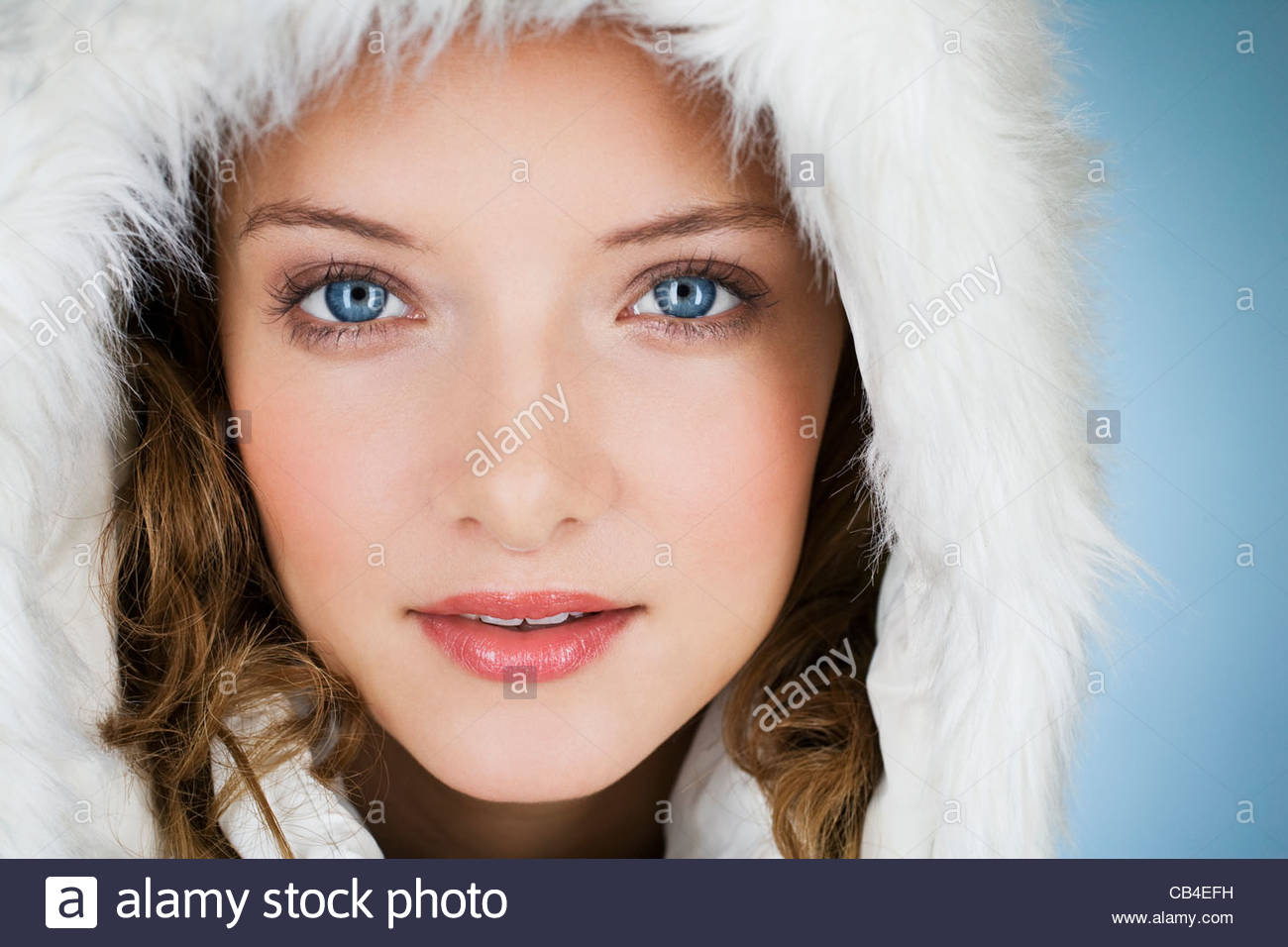 A young woman wearing a winter coat with a fur hood, close-up - Stock Image