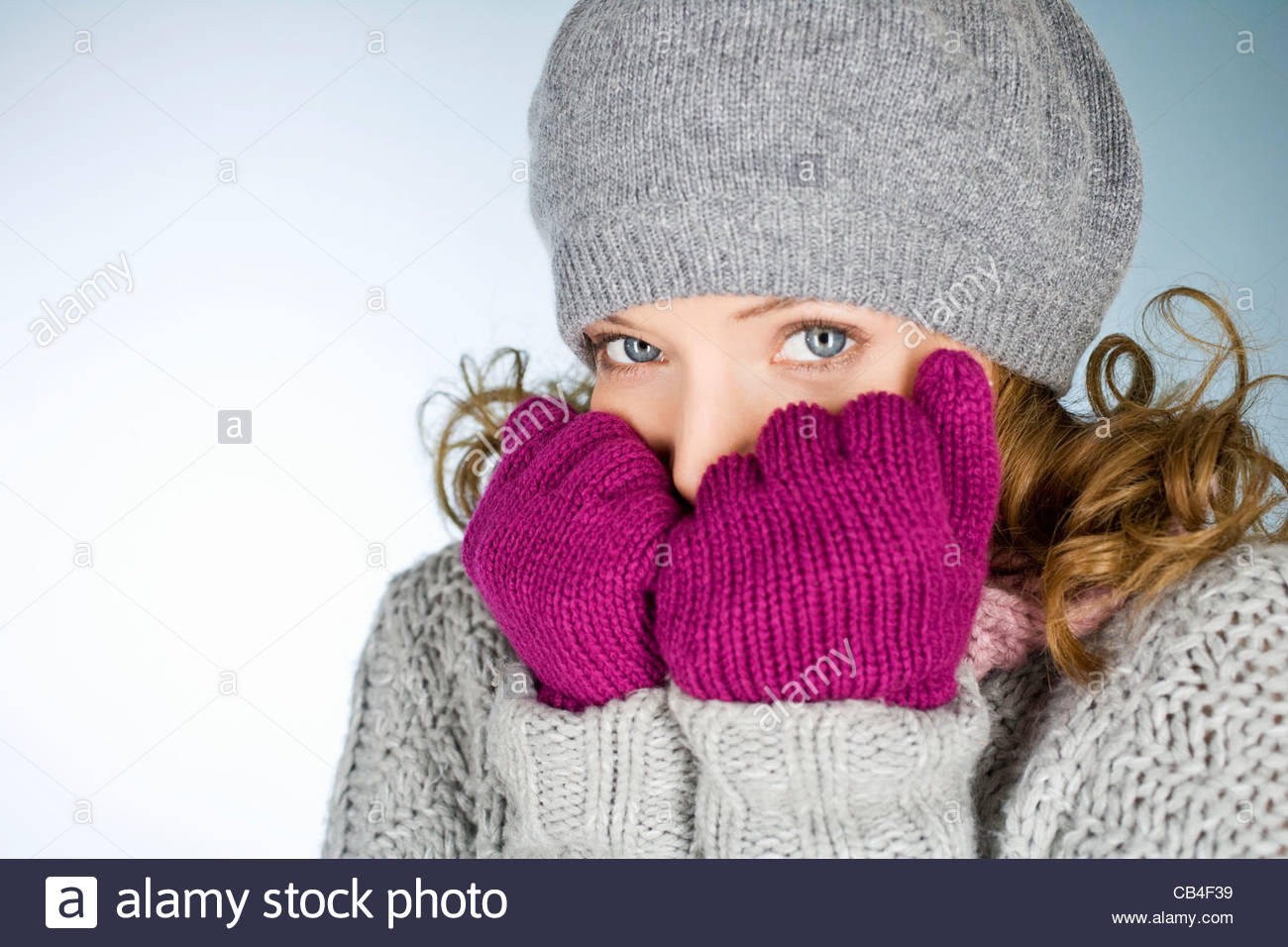 A young woman wearing hat and gloves, trying to keep warm - Stock Image