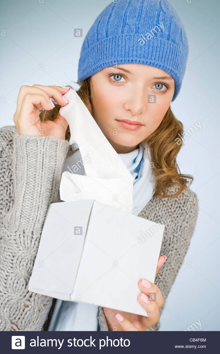 A young woman taking a tissue out of a tissue box - Stock Image