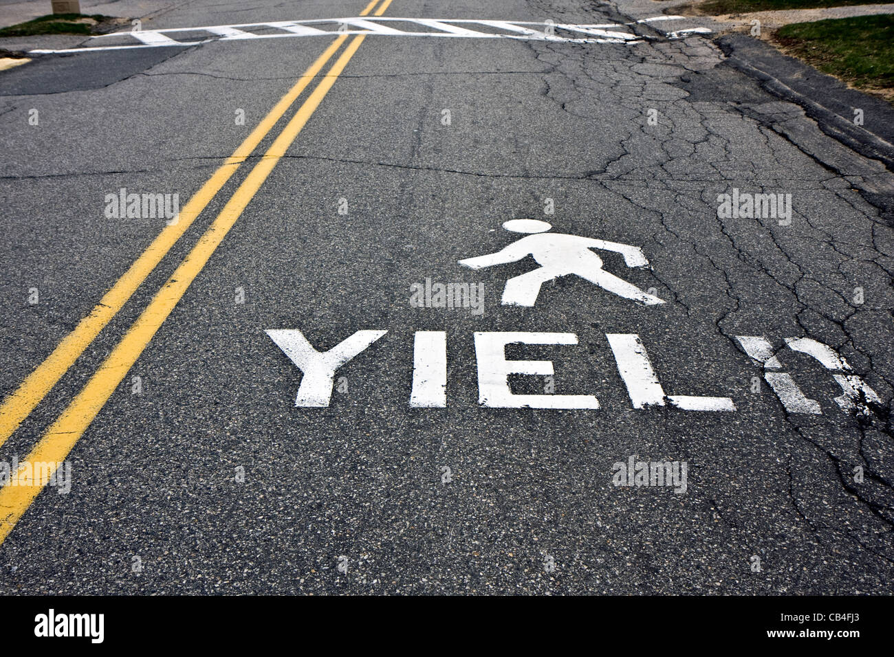 Warning at crossroad saying yield and person sign on asphalt - Stock Image
