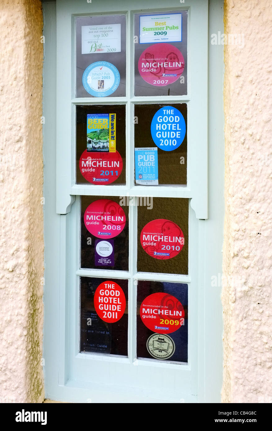 A window at the Gurnard's Head pub covered with Michelin Guide awards. - Stock Image