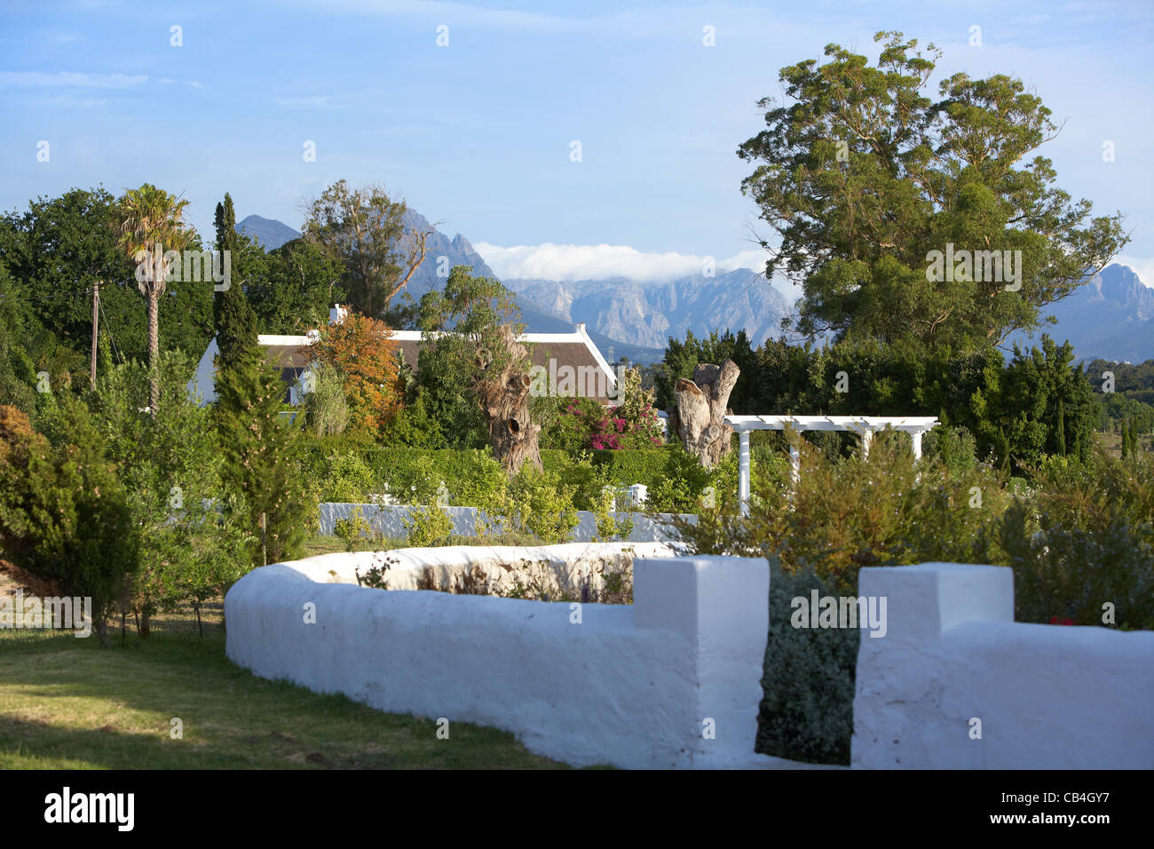 White garden wall and thatched roof with mountains near Stellenbosch
