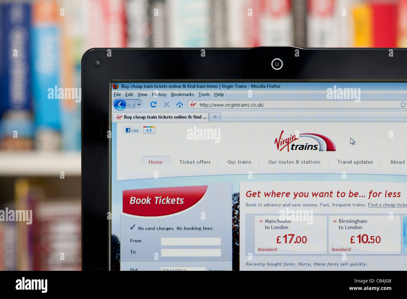 The Virgin Trains website shot against a bookcase background (Editorial use only: print, TV, e-book and editorial - Stock Image