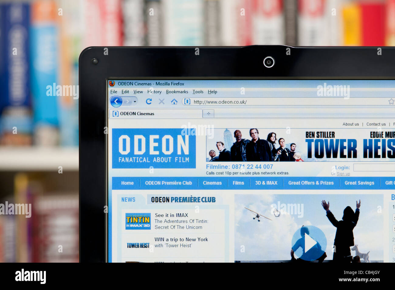 The Odeon website shot against a bookcase background (Editorial use only: ­print, TV, e-book and editorial - Stock Image