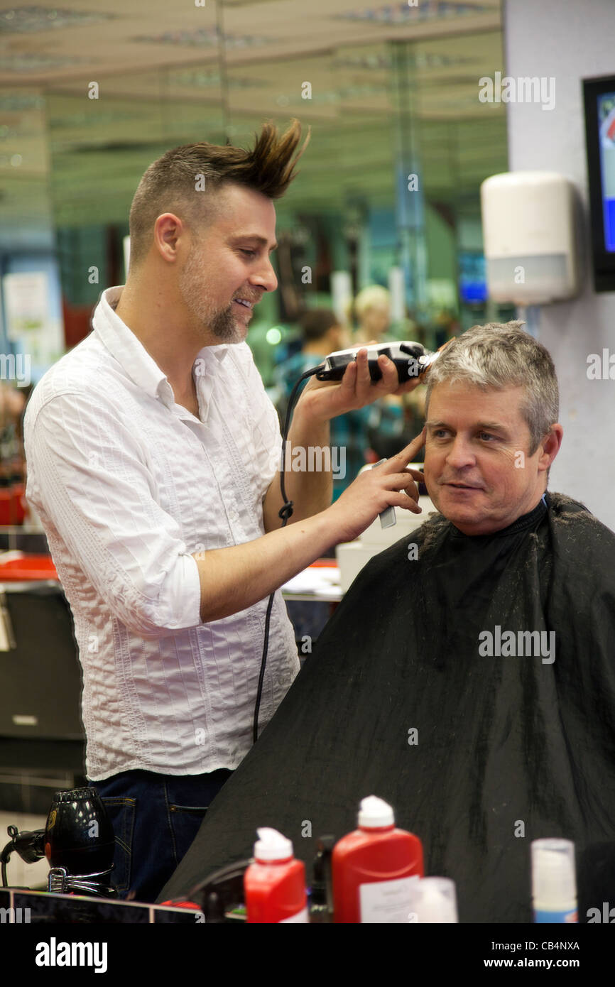 Mature man having haircut - Stock Image