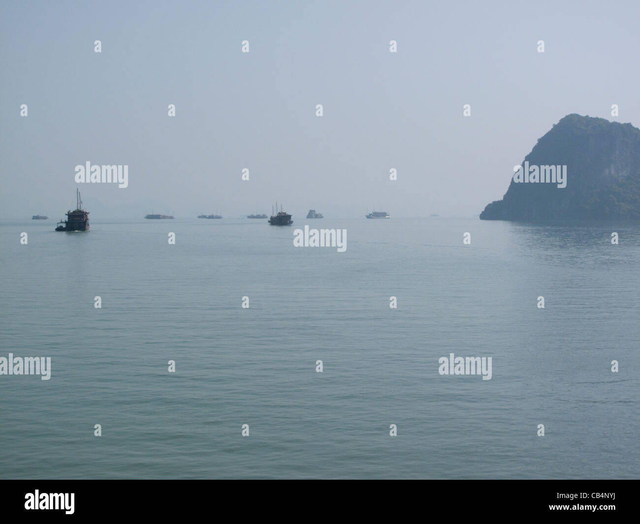 View of junk boats in the distance in Halong Bay, Vietnam - Stock Image
