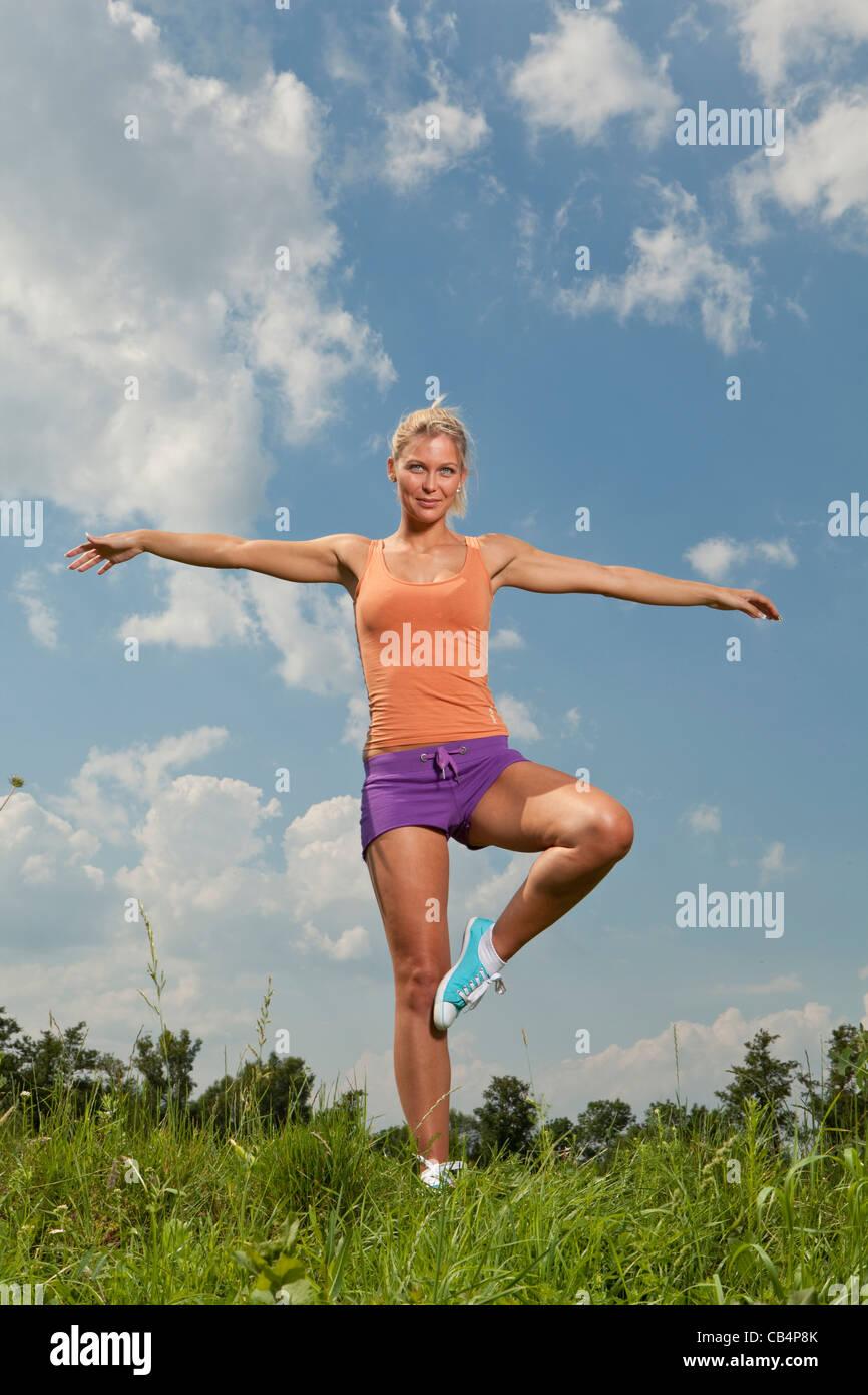 blond girl in nature green park, fitness program - Stock Image