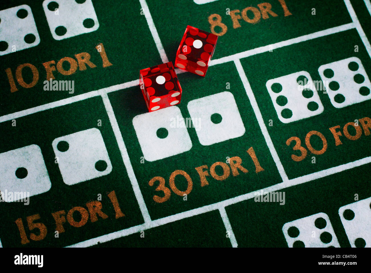 Casino dice roll snake eyes on a craps table felt - Stock Image