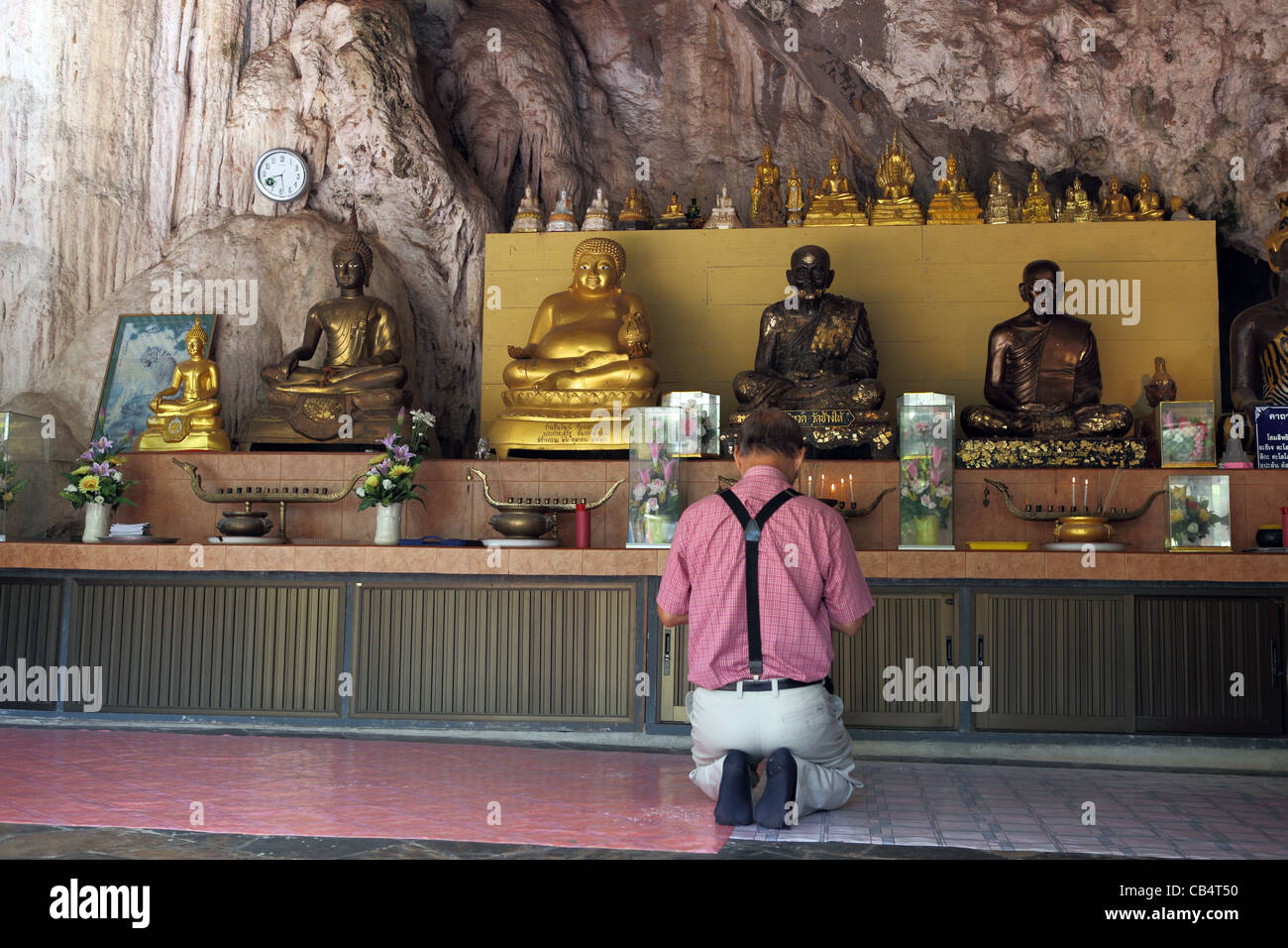 Man preying in front of Buddha statues at Wat Tham Seua (Tiger Cave) temple. Stock Photo