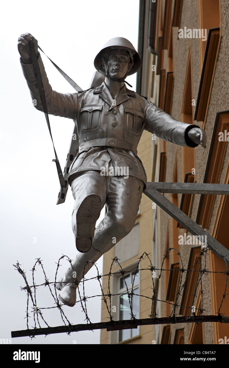 Sculpture of a soldier from the National People's Army jumping the fledgling Berlin Wall at Bernauer Strasse in Berlin, Germany. Stock Photo