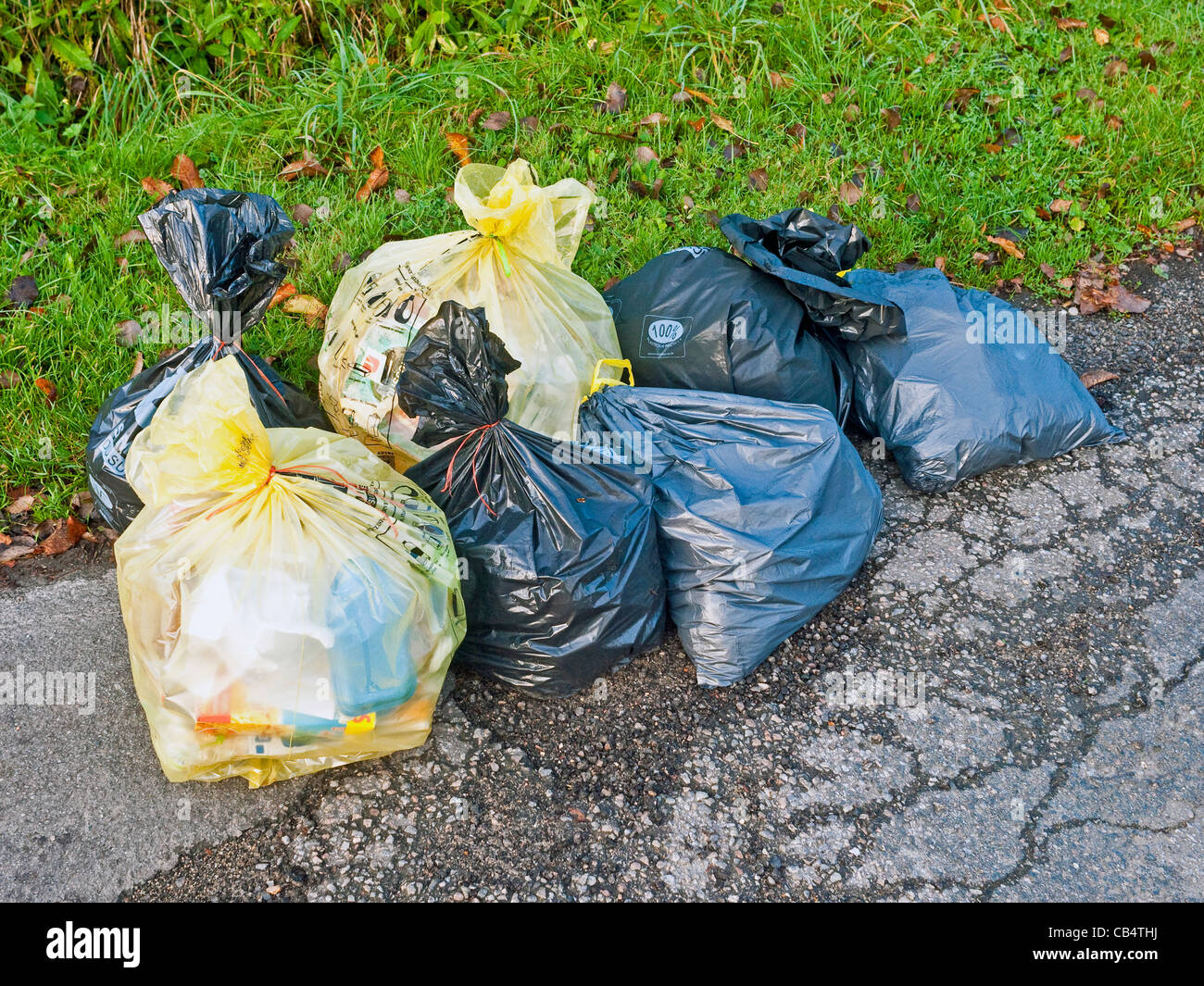 Household rubbish plastic sacks awaiting weekly collection - France. - Stock Image
